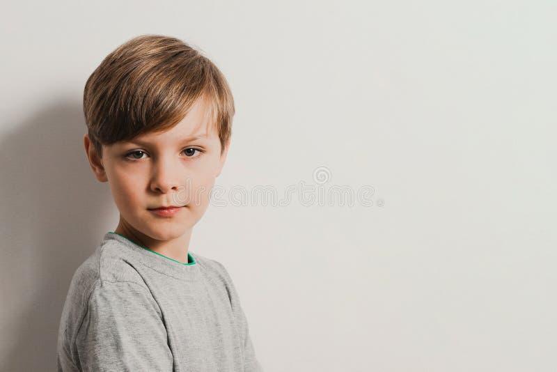 Stående av en gullig pojke i en grå skjorta, vid den vita väggen royaltyfri foto