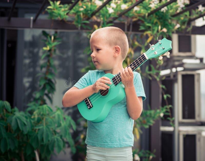 Stående av en gullig pojke med ukulelet royaltyfri bild