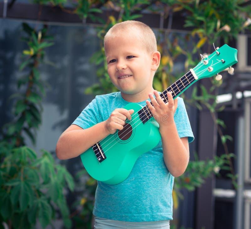 Stående av en gullig pojke med ukulelet royaltyfri fotografi