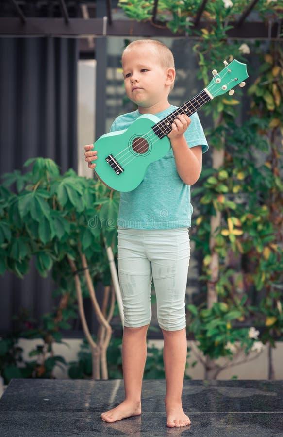 Stående av en gullig pojke med ukulelet fotografering för bildbyråer
