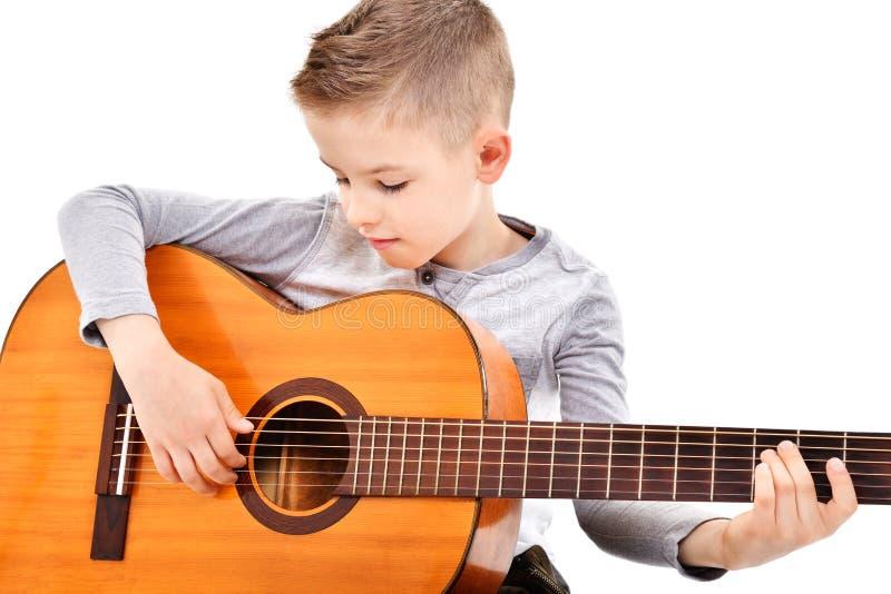 Stående av en gullig pojke som spelar den akustiska gitarren fotografering för bildbyråer