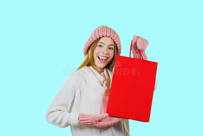 Stående av en gullig rödhårig flicka i en stucken hatt och tumvanten som rymmer en röd påse och ser kameran och skratta royaltyfria bilder
