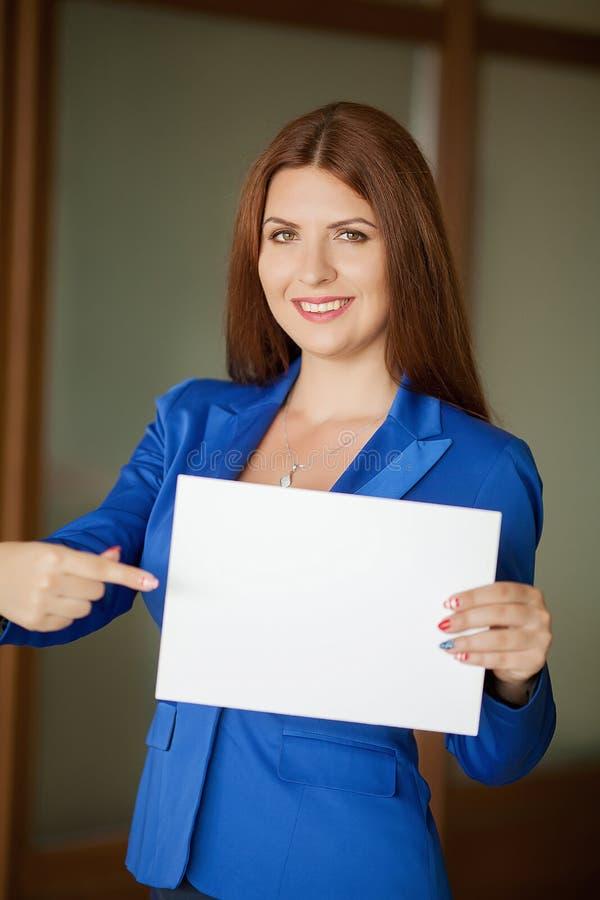 Stående av en gullig ung affärskvinna som ler, i en kontorsmiljö arkivfoto