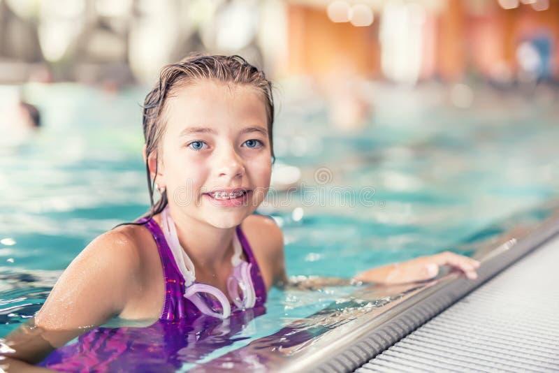 Stående av en gullig ung flicka med skyddsglasögon i simbassäng Simningutbildning arkivbilder