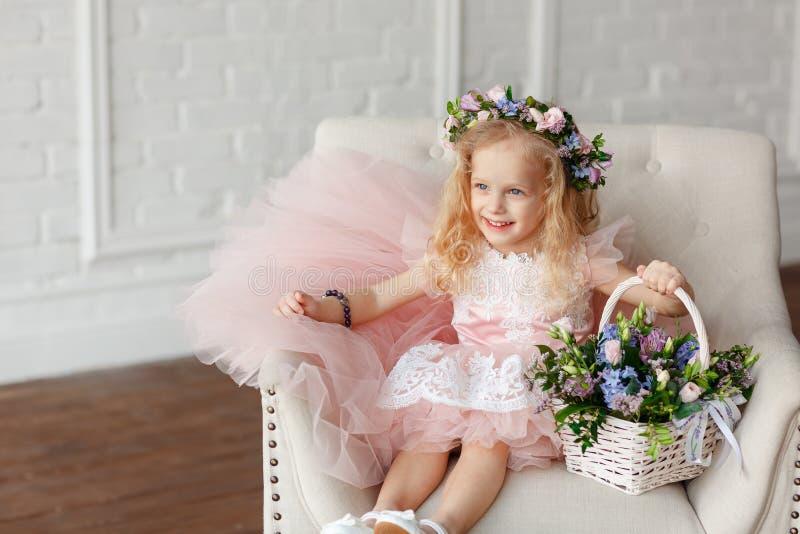 Stående av en gullig unge - flicka i a i en rosa klänning- och blommakrona Den härliga lilla flickan i en ljus studio sitter arkivfoton