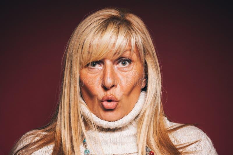 Stående av en häpen mogen kvinna - stående av den härliga mogna kvinnan med ett förvånat ansiktsuttryck - häpet kvinnabegrepp arkivfoton