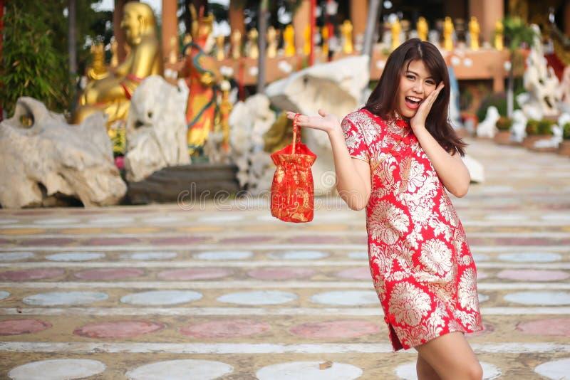 Stående av en härlig asiatisk kvinnahåll med lyckapengar och det röda facket, kinesiskt begrepp för nytt år arkivbilder