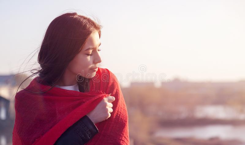 St?ende av en h?rlig asiatisk ton?rig flicka i profil, p? solnedg?ngen, med st?ngda ?gon i en r?d halsduk royaltyfria foton