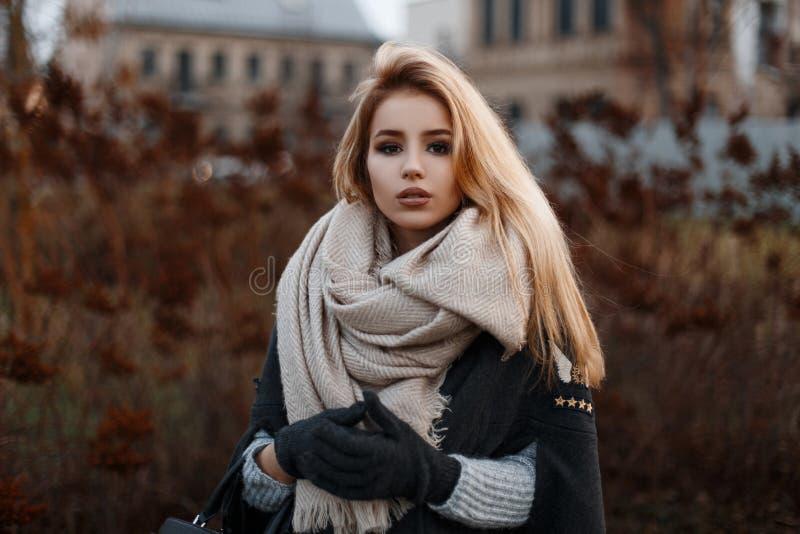 Stående av en härlig attraktiv ung flicka i ett stilfullt svart lag med en beige tappninghalsduk i svarta handskar royaltyfri foto