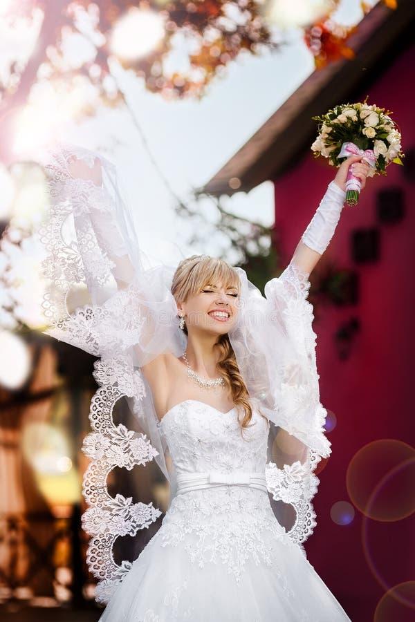 Stående av en härlig blond brud med bröllopbouqet fotografering för bildbyråer