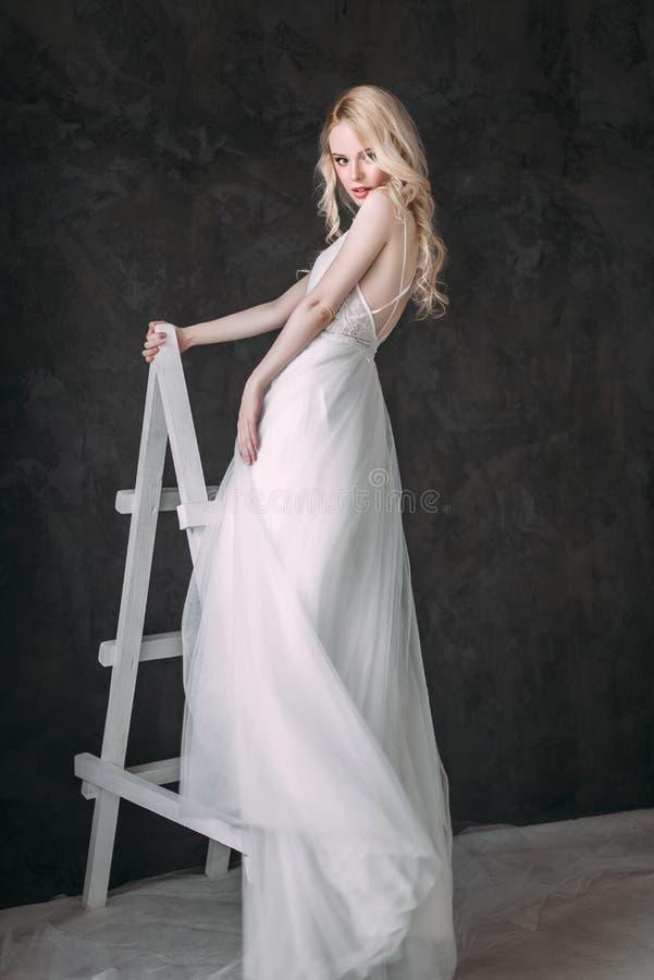 Stående av en härlig blond flicka i bilden av bruden Härlig le flicka Fotoet sköt i studion på en grå bakgrund arkivbilder