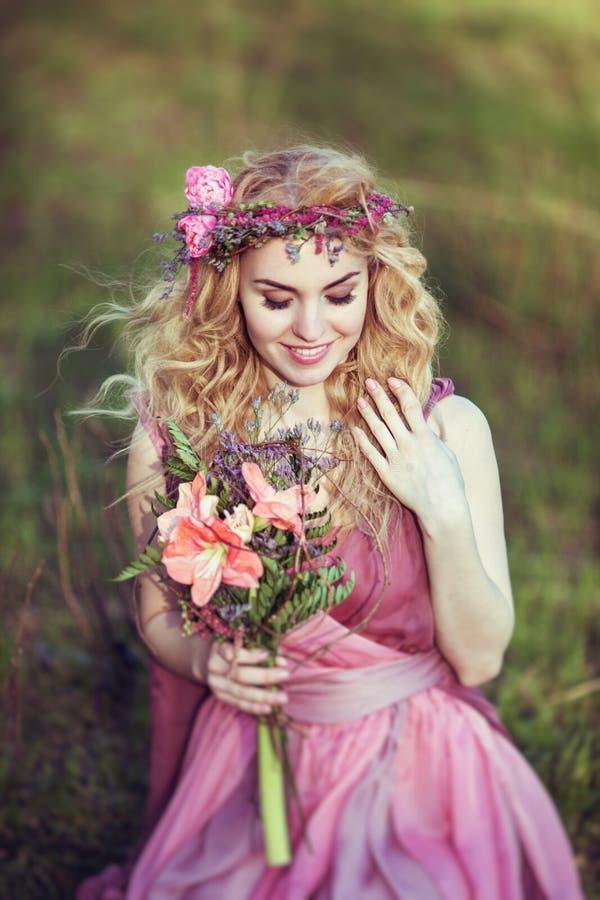 Stående av en härlig blond flicka i en rosa klänning med en bukett arkivfoton