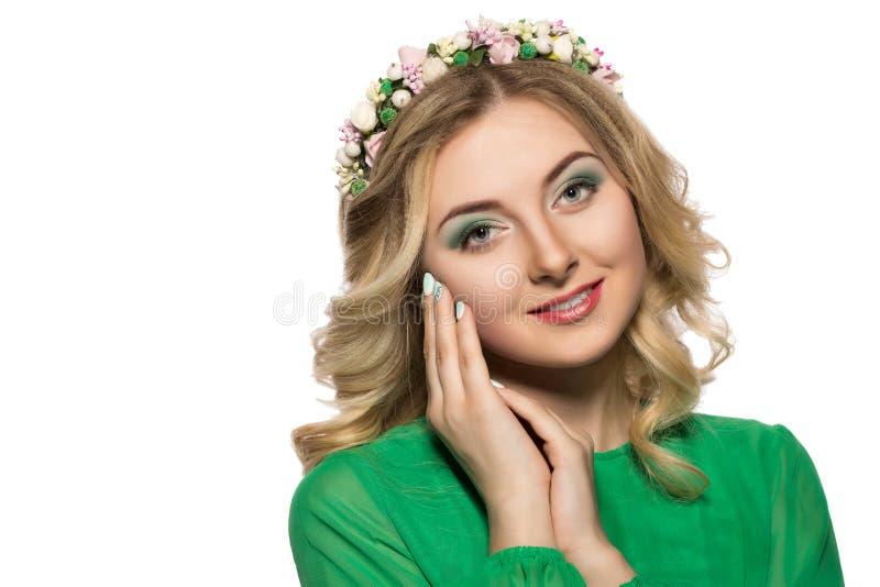 Stående av en härlig blond kvinna i en grön klänning som ser in i kameran och vikt hennes händer nära framsidan fotografering för bildbyråer