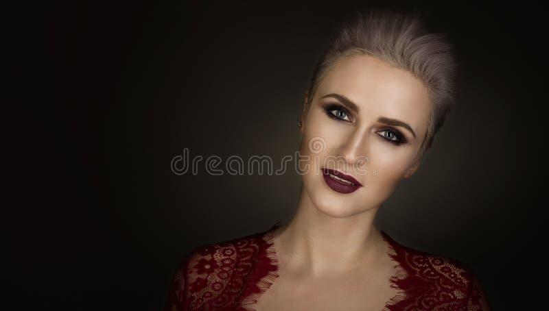 Stående av en härlig blond kvinna med kort hår och ljust smink arkivbild