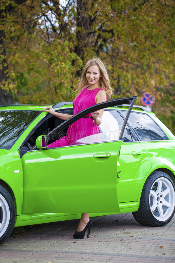 Stående av en härlig blond kvinna och gräsplansportbil royaltyfria bilder