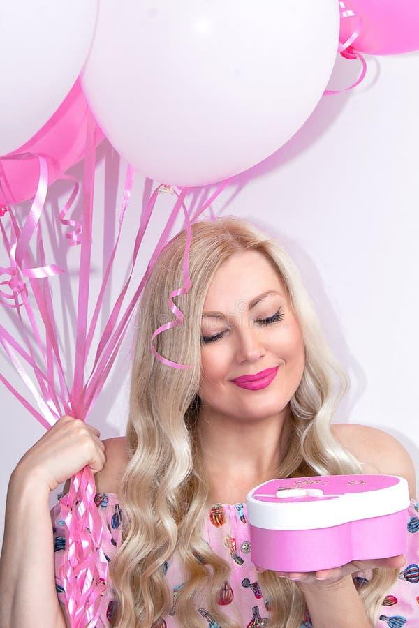 Stående av en härlig blond kvinna som rymmer en gåva, med rosa färg- och vitbollar Behar en gåva, överraskning Beröm royaltyfri foto