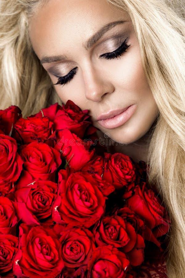 Stående av en härlig blond kvinnlig modell med långt härligt hår Modell i sexig damunderkläder som rymmer röda rosor royaltyfria bilder