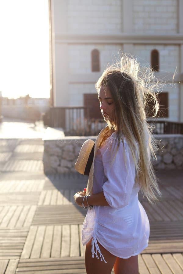 Stående av en härlig blond ung kvinna som tycker om solen på en solig sommarafton Resa resv?skan med seascapeinsida royaltyfria bilder