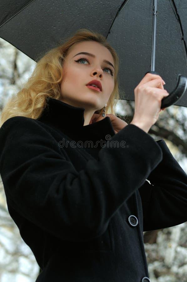 Stående av en härlig blondin som står under ett paraply arkivbilder