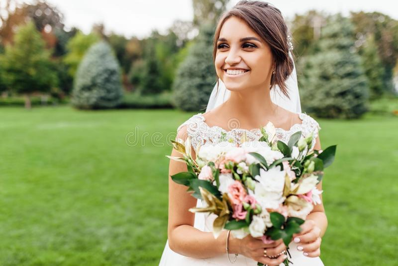 Stående av en härlig brud i natur, i en vit klänning fotografering för bildbyråer