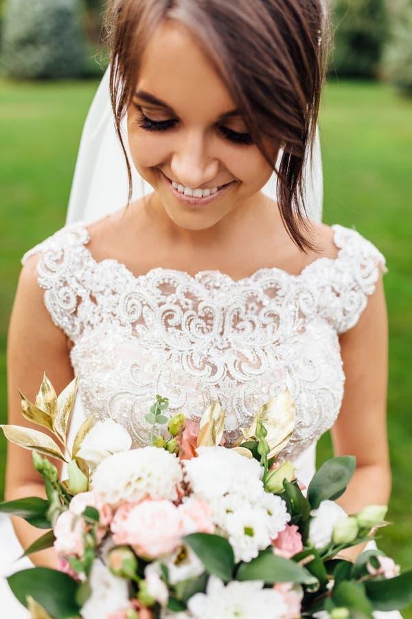Stående av en härlig brud i natur, i en vit klänning royaltyfri foto