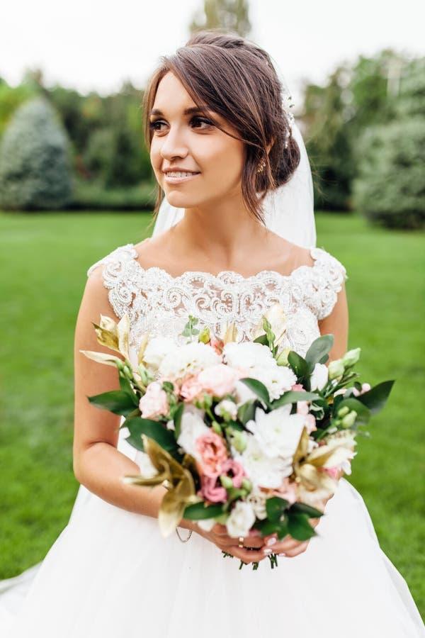 Stående av en härlig brud i natur, i en vit klänning arkivfoto
