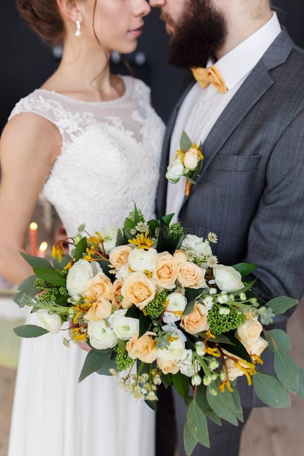 Stående av en härlig brud med en bukett och brudgummen med ett skägg fotografering för bildbyråer