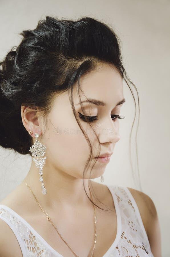 Stående av en härlig brunettflicka, makeup, falska ögonfrans, profil royaltyfri bild