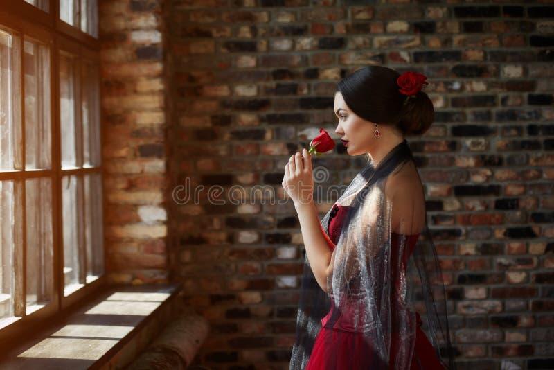 Stående av en härlig dansare för ung kvinna i en röd klänning nära fönstret arkivbilder