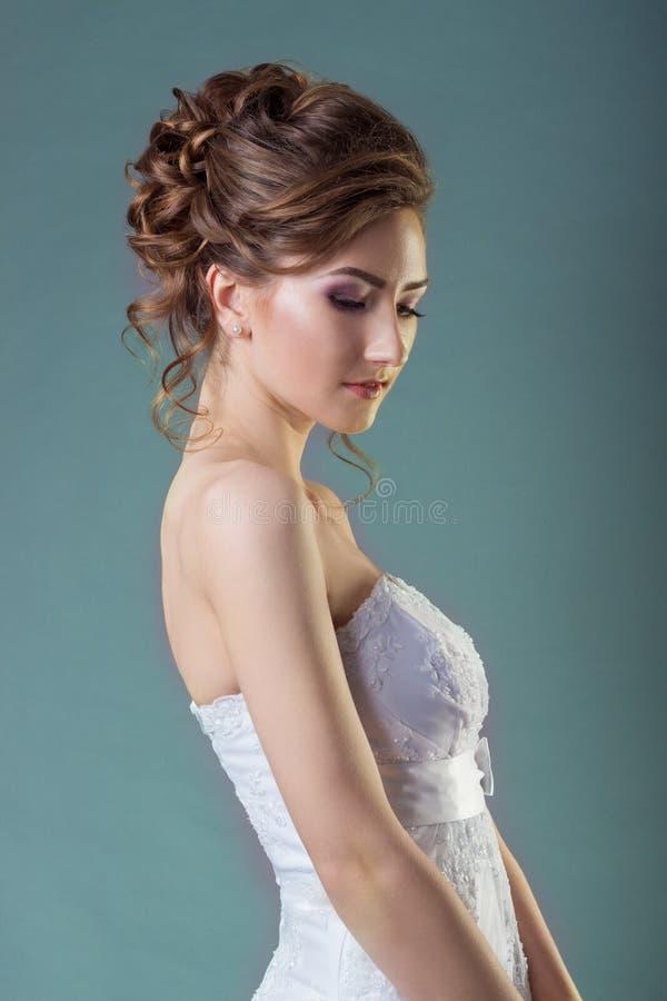 Stående av en härlig försiktig och elegant flickakvinnabrud i en vit klänning med en härlig frisyr och makeup arkivbild