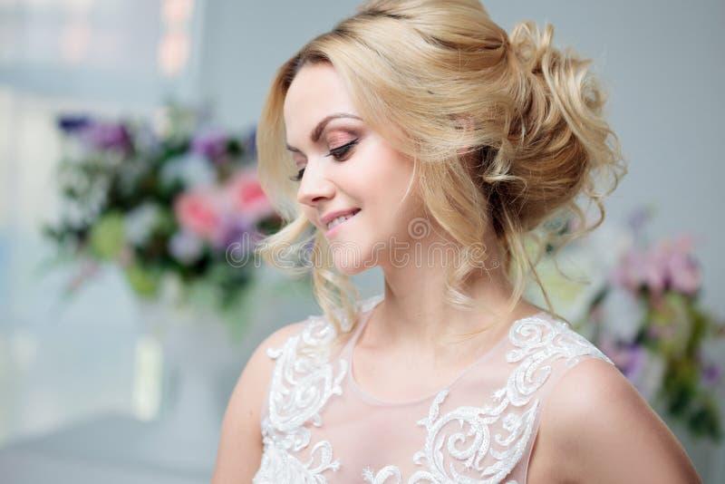 Stående av en härlig flicka i en bröllopsklänning Brud i en lyxig klänning på en vit bakgrund, härlig frisyr arkivfoto