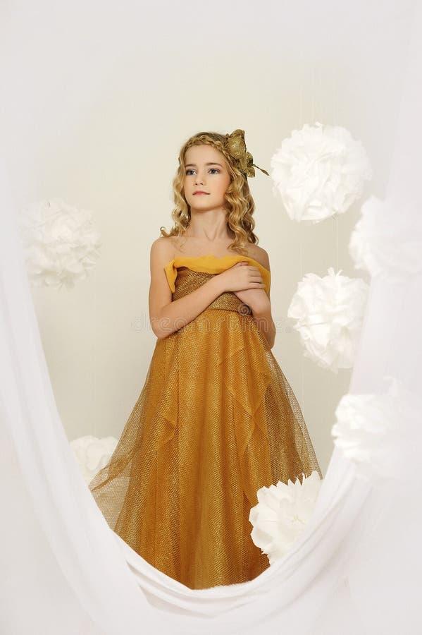 Stående av en härlig flicka i en guld royaltyfri bild