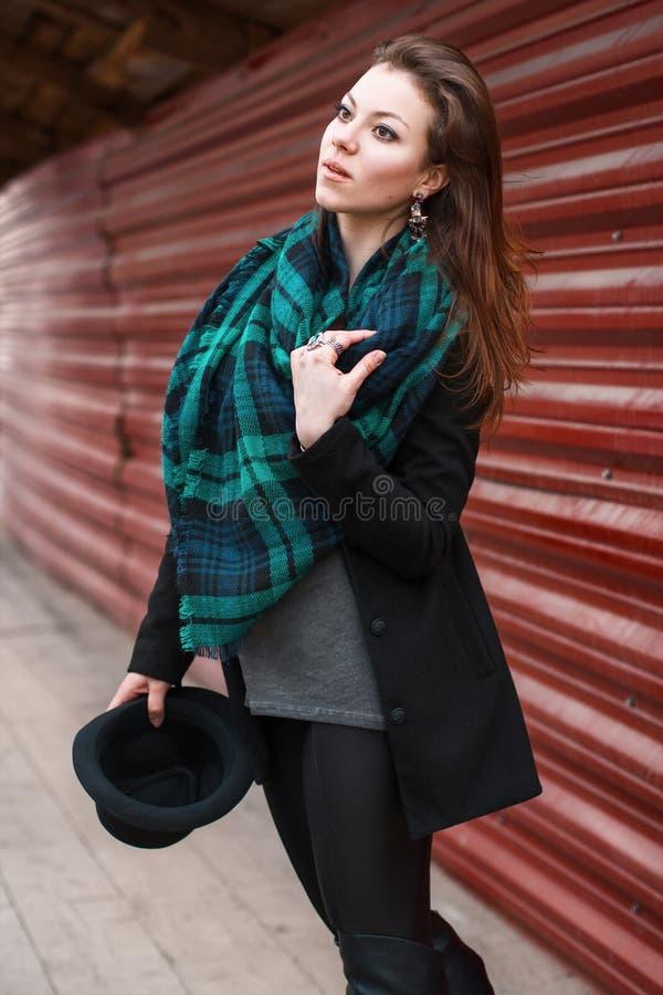 Stående av en härlig flicka i ett lag med en halsduk Hatt i hand arkivfoto