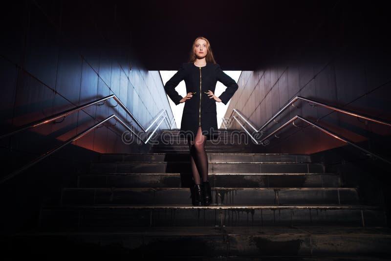 Stående av en härlig flicka i ett mörkt hall arkivfoto