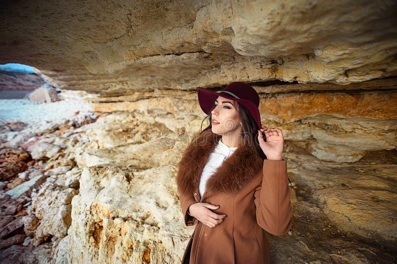 Stående av en härlig flicka i hatten på en bergbakgrund arkivfoto