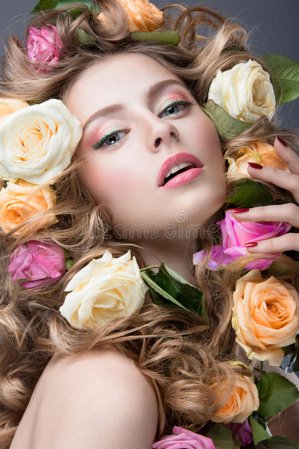 Stående av en härlig flicka med ett försiktigt rosa smink och massor av blommor i hennes hår Härlig le flicka royaltyfri foto