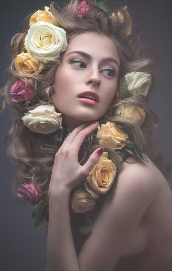Stående av en härlig flicka med ett försiktigt rosa smink och massor av blommor i hennes hår Spring avbildar Härlig le flicka royaltyfri foto