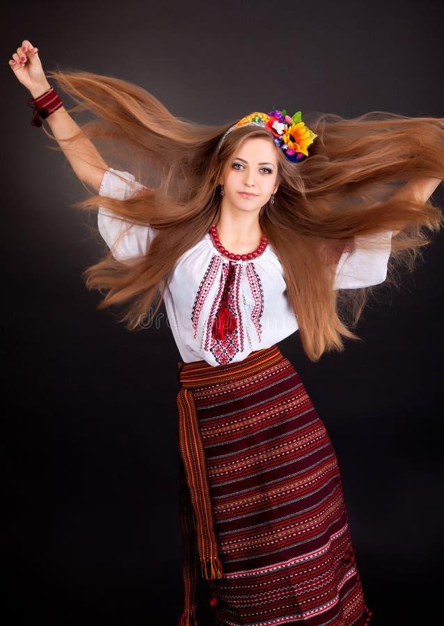 Stående av en härlig flicka med flygbrunthår. Kvinnan bär royaltyfri bild