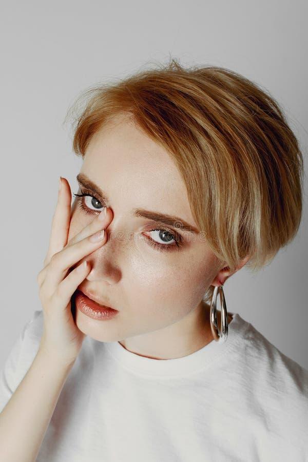 Stående av en härlig flicka med en kort frisyr på en vit bakgrund i en vit T-tröja fotografering för bildbyråer