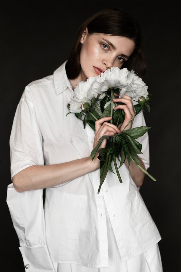 Stående av en härlig flicka med pioner Skönhet som retuscherar fotoet Mode och skönhetsmedelbegrepp grå studiobakgrund royaltyfri foto