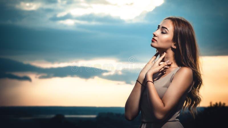 Stående av en härlig flicka mot bakgrunden av en molnig aftonhimmel på solnedgången, en ung kvinna i en sommarklänning res royaltyfria foton