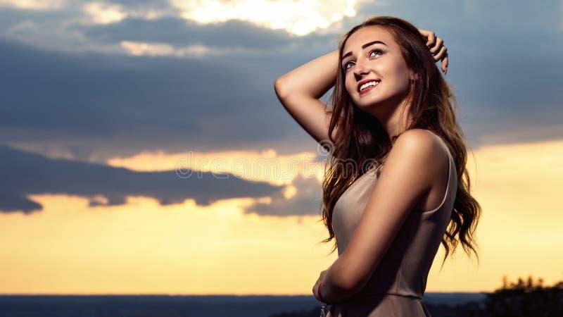 Stående av en härlig flicka mot bakgrunden av en molnig aftonhimmel på solnedgången, en ung kvinna i en sommarklänning som vilar  royaltyfri foto