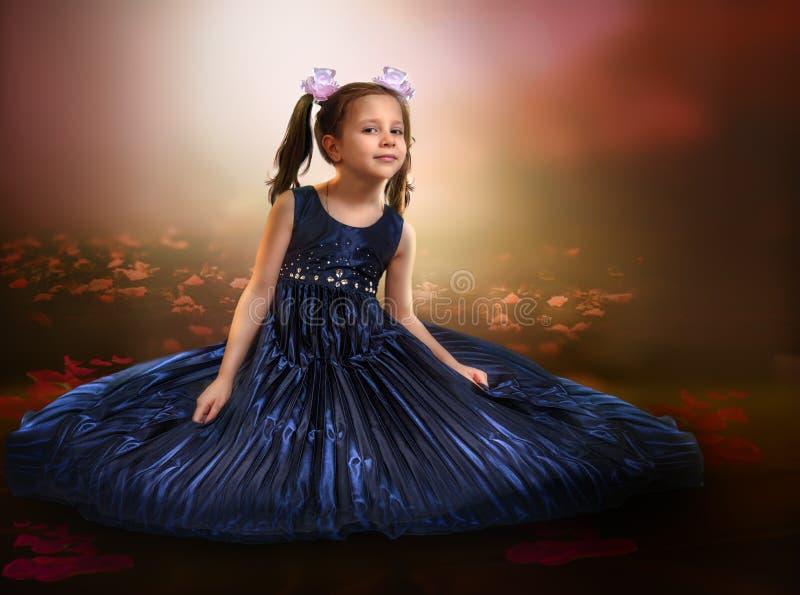 Stående av en härlig flicka på en abstrakt bakgrund som sitter fotografering för bildbyråer