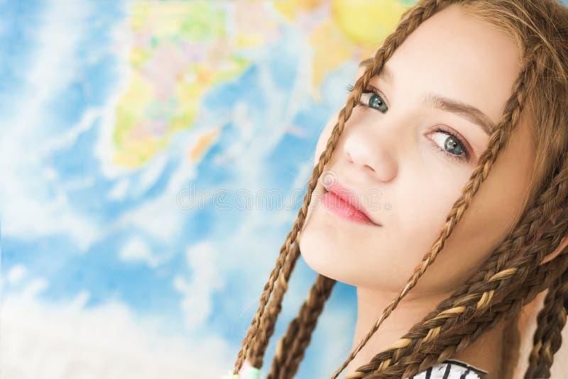 Stående av en härlig flickaframsidanärbild på en världskartabakgrund Mjukt naturligt ljus arkivfoto