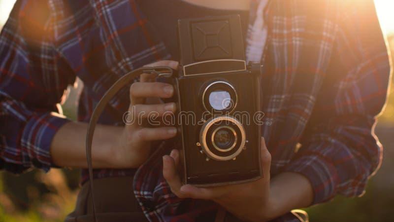 Stående av en härlig flickahipster med den retro filmkameran för tappning fotografering för bildbyråer