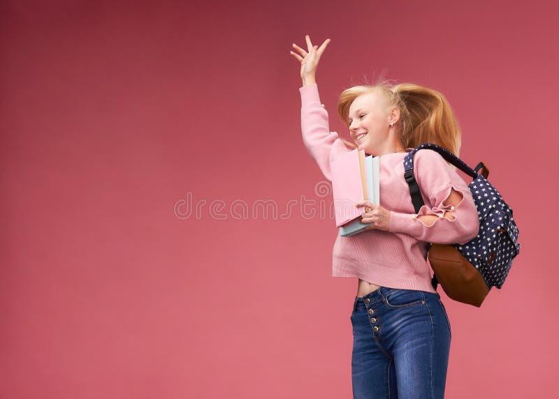 Stående av en härlig flickastudent med en ryggsäck och en lärobok boken i händerna av att le på en rosa bakgrund arkivfoton