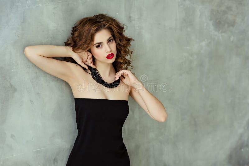 Stående av en härlig glamorös brunett med lockigt hår och b royaltyfria bilder