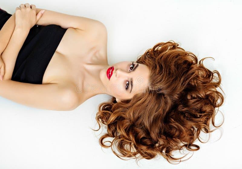 Stående av en härlig glamorös brunett med lockigt hår och b arkivbild