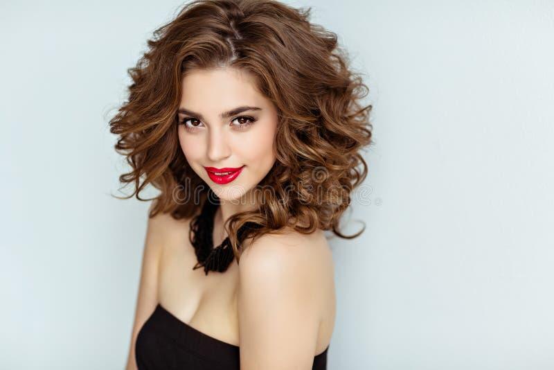 Stående av en härlig glamorös brunett med lockigt hår och b arkivfoton
