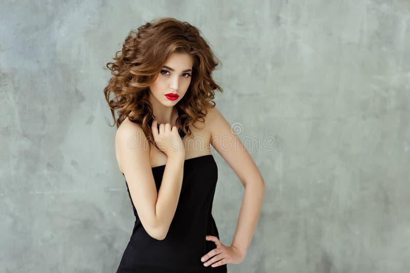 Stående av en härlig glamorös brunett med lockigt hår och b arkivfoto